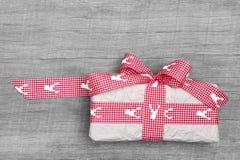 Eingewickeltes Weihnachtsgeschenk mit einem roten Band mit Elchen Lizenzfreie Stockfotos