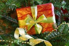 Eingewickeltes Weihnachtsgeschenk nahe dem Weihnachtsbaum Stockfoto