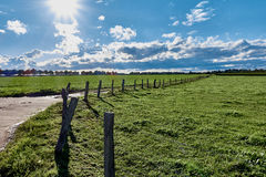 Eingezäunte Weiden nach rechts nach einem Gewitter, wenn die Sonne durch ländliches Gebiet einläuft Stockbild