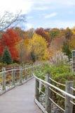 Eingezäunter Weg unter den Herbstbäumen Lizenzfreies Stockfoto