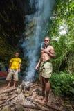 Einheimische der Insel Neu-Guinea haben Abendessen und das gemachte Feuer, zum des Lebensmittels zu kochen Lizenzfreies Stockfoto