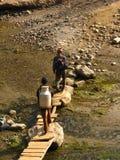 Einheimische, die auf dem Weg eine kleine Brücke zu Pokhara kreuzen Lizenzfreie Stockfotografie