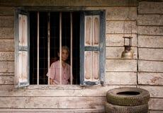 Einheimische Dorffrau, die vom Fenster des Holzhauses schaut lizenzfreies stockfoto
