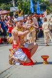 Einheimischer Tänzermann mit dem traditionellen Kostüm, das Behälter mit hält Stockfotografie