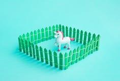 Einhornspielzeugmodell im Zaun auf Farbe stockbilder
