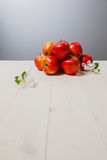 Einige Äpfel auf einer weißen Holzoberfläche lizenzfreie stockfotografie