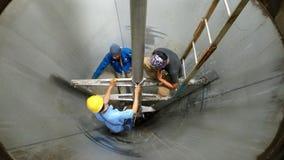 Einige Arbeitskräfte arbeiten in den Behältern auf Bauvorhaben Stockfotografie