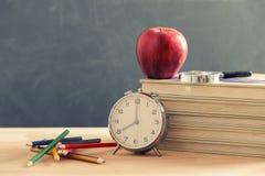 Einige Bücher und eine Bleistifthalterung auf einer hölzernen Tabelle Roter Apfel steht auf den Büchern Stockbilder
