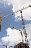 Einige Baukräne, die am Mittag arbeiten Lizenzfreie Stockfotos