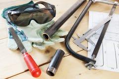 Einige Bauschlosserarbeitsgeräte auf dem hölzernen Werktisch Lizenzfreie Stockbilder