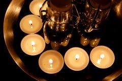 Einige beleuchtete Teelichter steht auf einer metallischen Oberfläche um kleine Glasflaschen stockfotos