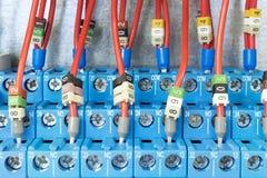 Einige blaue Drähte des Zwischenrelais werden entsprechend dem Entwurf angeschlossen Das Relais wird an der Schiene auf der Leite Stockfoto