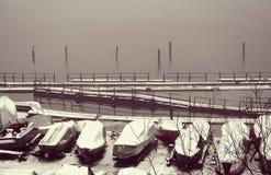 Einige Boote bedeckt mit Schnee nahe dem Ufer bedeckt im Hintergrund fängt an einzufrieren, bedeckt mit dünnem Eisfluß Lizenzfreie Stockbilder