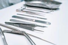 Einige chirurgische Instrumente liegen auf einer wei?en Tabelle stockbild