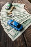 Einige 100-Dollar-Banknoten im Halbrundplan mit einer Grundstellungstaste und Spielzeugautos auf der gealterten rauen Holzoberflä Lizenzfreie Stockfotografie