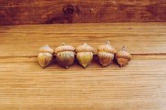 Einige Eicheln auf dem Holztisch stockbild