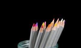 Einige farbige Bleistifte im Glas auf einem dunklen Hintergrund Lizenzfreie Stockfotos
