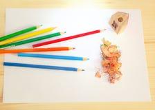 Einige farbige Bleistifte und Bleistiftspitzer Lizenzfreie Stockfotografie
