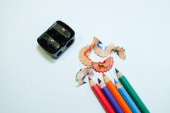 Einige farbige Bleistifte von verschiedenen Farben und Bleistiftspitzer und Bleistift, die auf Weißbuchhintergrund rasieren Lizenzfreie Stockfotografie