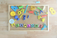 Einige farbige Würfelbuchstaben auf einer Tafel in einem Klassenzimmer, welches das Wort bildet, ERFORSCHEN Stockfotos