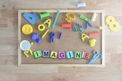 Einige farbige Würfelbuchstaben auf einer Tafel in einem Klassenzimmer, welches das Wort bildet, STELLEN sich vor Stockbilder