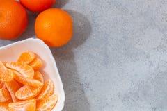 Einige ganze und abgezogene reife Tangerinen auf einer weißen Platte auf grauem Hintergrund mit Raum für Text, flache Lage, Drauf lizenzfreies stockbild
