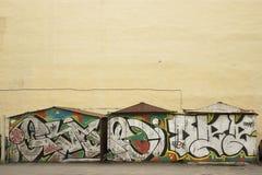 Einige Garagen mit Graffiti nahe der gelben Wand Stockbilder