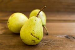 Einige gelbe Birnen sind auf dem Holztisch stockbild