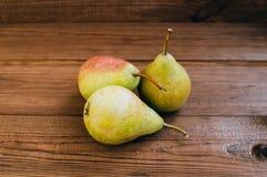 Einige gelbe Birnen sind auf dem Holztisch stockbilder