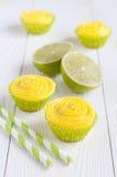 Einige gelbe kleine Kuchen in den Papierzwischenlagen Stockfotografie