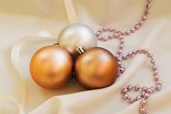 Einige goldene Weihnachtsbälle auf dem weißen Gewebe lizenzfreies stockfoto