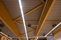 Einige große hölzerne Binder stützen das Dach eines großen Fabrikgebäudes lizenzfreie stockfotografie