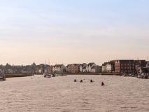 Einige Kajaks, die hinunter Fluss rudern, strömen in Hafen im wivenhoe lizenzfreies stockbild