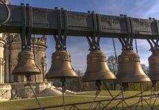 Einige kleine kupferne Glocken hängen an einem großen Holzbalken nahe der Kirche Kirche des Zeichens der gesegneten Jungfrau im D lizenzfreies stockfoto