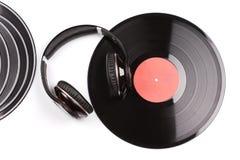 Einige kleine und ein große schwarze Vinylaufzeichnungen neben eleganten Kopfhörern lizenzfreie stockbilder