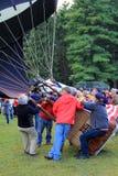Einige Leute, die zusammenarbeiten, um Ballone für Flug, Ballon-Festival, Crandall-Park, Glens Falls, New York, 2014 zu füllen Stockbild