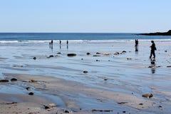 Einige Leute im Schatten gehend entlang kurze Sande setzen, Maine, 2018 auf den Strand Lizenzfreie Stockfotos