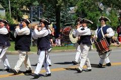 Einige Männer im Zeitraumkostüm, marschierend in am 4. Juli Parade, Saratoga Springs, New York, 2016 Stockbild