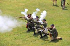 Einige Männer kleideten in Soldat ` s Uniformen, unter Verwendung der Gewehre während der Kriegswiederinkraftsetzungen, Fort Onta Lizenzfreies Stockbild