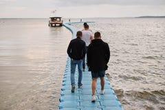 einige männliche Freunde gehen entlang ein Plastikpierdock mit Kopienraum, einzeln aufführen vom männlichen Gehen, zum Pier zu ge lizenzfreie stockbilder