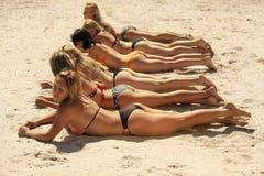 Einige Mädchen im Bikini, der auf sandigem Strand liegt Lizenzfreies Stockbild