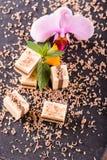 Einige Nugatwürfel auf Schieferplatte mit Orchidee blühen lizenzfreies stockfoto