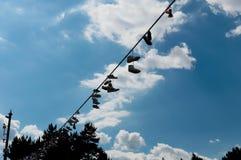 Einige Paare Turnschuhe, die an einem Seil gegen den blauen Himmel hängen Stockfotografie