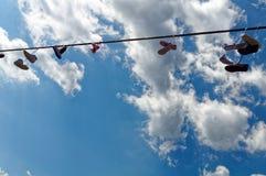 Einige Paare Turnschuhe, die an einem Seil gegen den blauen Himmel hängen Lizenzfreie Stockbilder