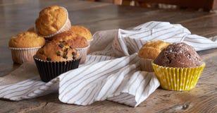 Einige verschiedene Muffins auf einem Holztisch Stockfotografie