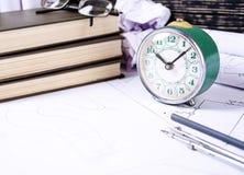 Einige Werkzeuge für das Zeichnen, Gläser und Retro- Uhr liegend in den Zeichnungen lizenzfreies stockfoto