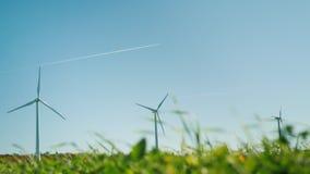 Einige Windturbinen Im Vordergrund gibt es ein grünes Gras, im Hintergrund, den ein Flugzeug in den Himmel fliegt stock video
