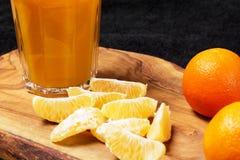Einiges reife Zitrusfrucht und ein Glas Saft auf einem Holztisch auf einer Tafel - Mandarinen Lizenzfreie Stockbilder