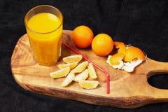 Einiges reife Zitrusfrucht und ein Glas Saft auf einem Holztisch auf einer Tafel - Mandarinen Lizenzfreie Stockfotografie