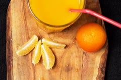 Einiges reife Zitrusfrucht und ein Glas Saft auf einem Holztisch auf einer Tafel - Mandarinen Lizenzfreie Stockfotos